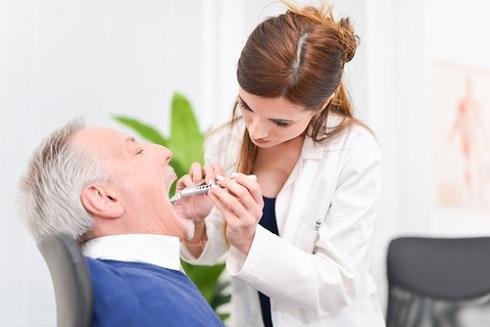 Врач осматривает рот пациента