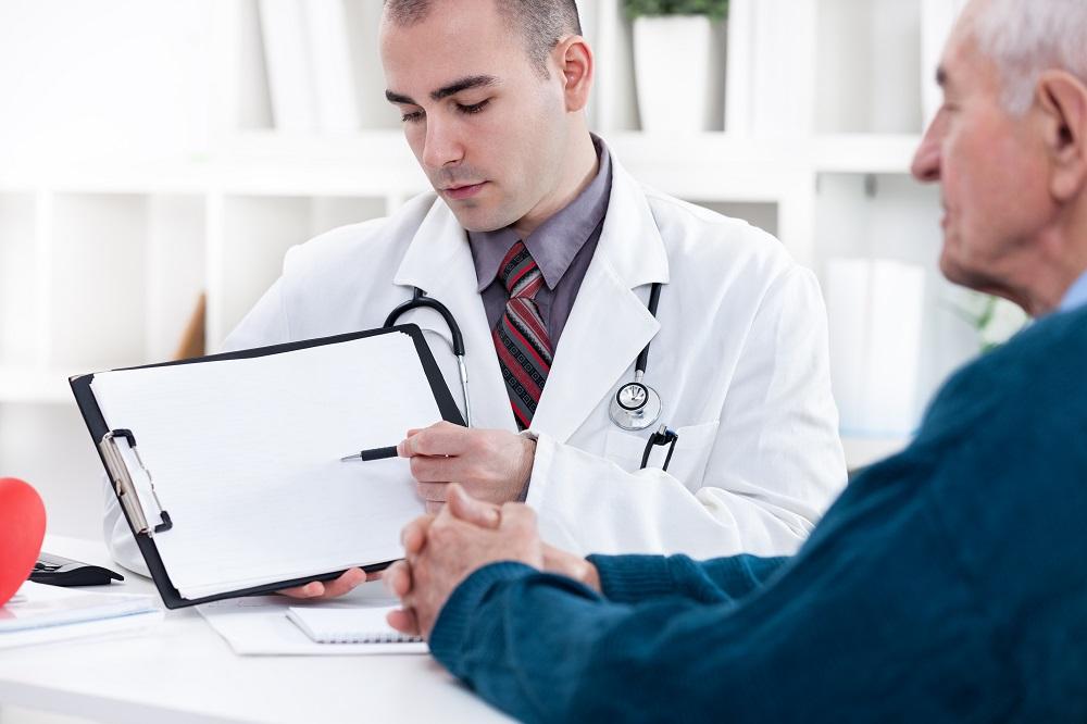 Herzspezialist erklärt dem Patienten sein Elektrokardiogramm (EKG)